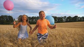 Couple of happy little kids with balloons in arms jogging through wheat field. Small girl and boy holding hands of each