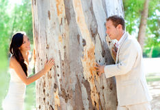 Couple happy in love playing in a tree trunk Royalty Free Stock Images