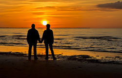 Couple of happy seniors at a beach of the Baltic Sea during sunset. Image was taken by summer in Jurmala  -  famous resort in Latvia, Europe Royalty Free Stock Photo