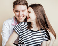Couple of happy smiling teenagers students, warm colors having a kiss, lifestyle people concept, boy and girl together Royalty Free Stock Photos