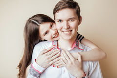 Couple of happy smiling teenagers students, warm colors having a kiss, lifestyle people concept Royalty Free Stock Image