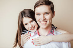 Couple of happy smiling teenagers students, warm colors having a kiss, lifestyle people concept Stock Photo