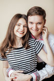 Couple of happy smiling teenagers students, warm colors having a kiss, lifestyle people concept Stock Photography