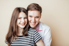 Couple of happy smiling teenagers students, warm colors having a kiss, lifestyle people concept Royalty Free Stock Photos