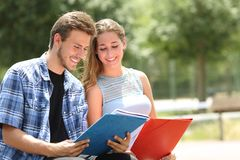 Couple of students studying together in a campus. Couple of happy students studying together sitting in a campus royalty free stock photo