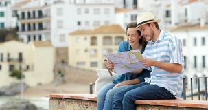 Couple of tourists talking and checking map stock footage