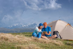 Couple of happy travelers sit next to tent and use tablet Royalty Free Stock Photo
