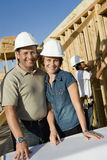 Couple In Hardhats With Blueprint At House Construction Site Royalty Free Stock Image