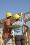 Couple In Hardhats With Blueprints At Building Site Stock Photography