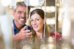 Couple in hardware store looking for lamps Royalty Free Stock Image