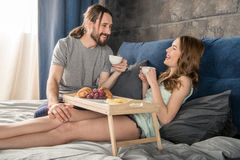 Couple has breakfast in bed. Young relaxed couple has breakfast and drinks coffee while lying in bed Stock Image