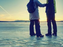 Couple has fun during winter walk on ice of frozen lake. Evening hike at beach of pond. Warm clothes pair with high warm boots two traveler sunrise smile sea royalty free stock image