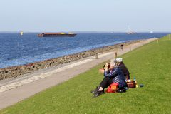 Couple enjoys a picknick at the dike and the panorama of the lake IJsselmeer, Flevoland, Netherlands. Couple is sitting on the dike with a picknick basket at the Royalty Free Stock Photography
