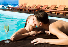 Couple has a rest in the pool with champagne. they are smiling, hugging and kissing. Royalty Free Stock Image