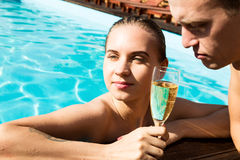 Couple has a rest in the pool with champagne. they are smiling, hugging and kissing. Stock Photos