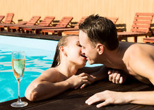 Couple has a rest in the pool with champagne. they are smiling, hugging and kissing. Royalty Free Stock Photography