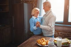 This couple has a splendid time dancing in the kitchen and remem stock photos