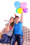 Couple with hats and balloons sitting on the couch Royalty Free Stock Photo
