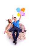 Couple with hats and balloons sitting on the couch Stock Photo