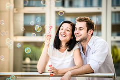 Couple have fun with bubble blower Royalty Free Stock Photos