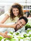 Couple have fun choosing flower in a greenhouse. Lovely couple have fun choosing flower in a greenhouse Royalty Free Stock Images