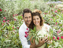 Couple have fun choosing flower pots in a greenhouse. Couple have fun choosing flower pots Royalty Free Stock Photos