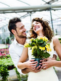 Couple have fun choosing flower pots in a greenhouse. Beautiful couple have fun choosing flower pots in a greenhouse Stock Images