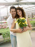 Couple have fun choosing flower pots in a greenhouse. In spring Royalty Free Stock Photography