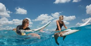 Couple have fun in outdoor infinity pool. Couole swimming with surf and relax in ocean Stock Image