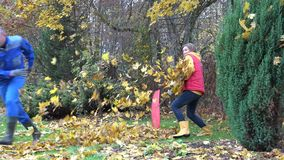 Couple have fun raking autumnal leaves in garden. 4K. Young couple have fun raking autumnal leaves in garden. 4K stock footage