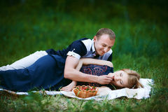 Couple have rest at picnic in forest. Lovers having picnic in forest. Blond girl in dark blue dress and men in light trousers and shirt. couple looking to each Royalty Free Stock Photos
