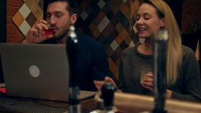 A couple have video chat via laptop with friends in a restaurant stock video