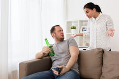 Couple having argument at home. People, relationship difficulties, conflict and family concept - angry women having argument with men drinking beer and watching Royalty Free Stock Photos