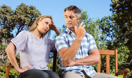 Couple having an argument on park bench royalty free stock image