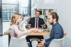 Couple having argument. Side view of couple having argument during meeting with lawyer in office stock image