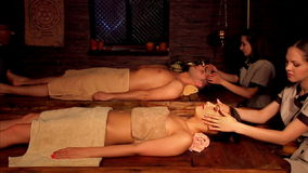Couple having Ayurvedic spa treatment. Two masseuses start to massage face.