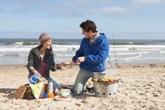 Couple Having Barbeque On Winter Beach Stock Photography