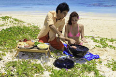 Couple having a beach barbecue Stock Images