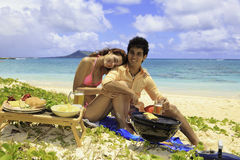 Couple having a beach barbecue Stock Photo