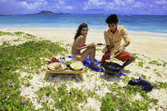 Couple having a beach barbecue Royalty Free Stock Photo