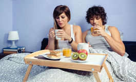 Couple having breakfast in bed served over tray Stock Photo