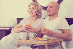 Couple having breakfast in bed Stock Photos