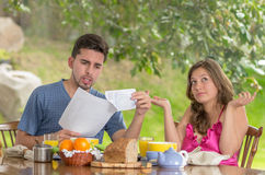 Couple having breakfast fighting over bills at Royalty Free Stock Photography