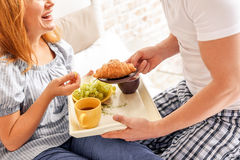 Couple having breakfast at home. Taking care of family members. man holding plate with croissant and offering it for woman during breakfast royalty free stock photography