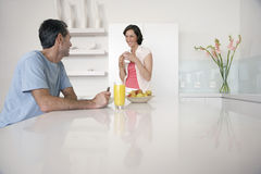 Couple Having Breakfast At Kitchen Bench Royalty Free Stock Photo