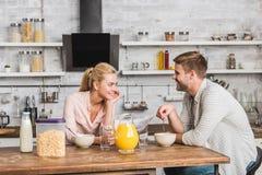 Couple having breakfast in kitchen girlfriend. Holding newspaper stock photos