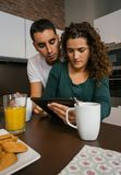 Couple having breakfast and looking tablet Stock Photos
