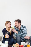 Couple having a breakfast. Man giving a green apple to his wife stock photo