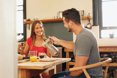 Couple having breakfast, man serving coffee. Royalty Free Stock Images