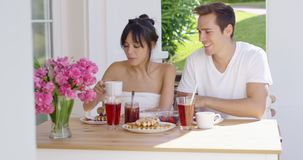 Couple having breakfast at outdoor table. With pink flowers in vase and green grass in background stock footage